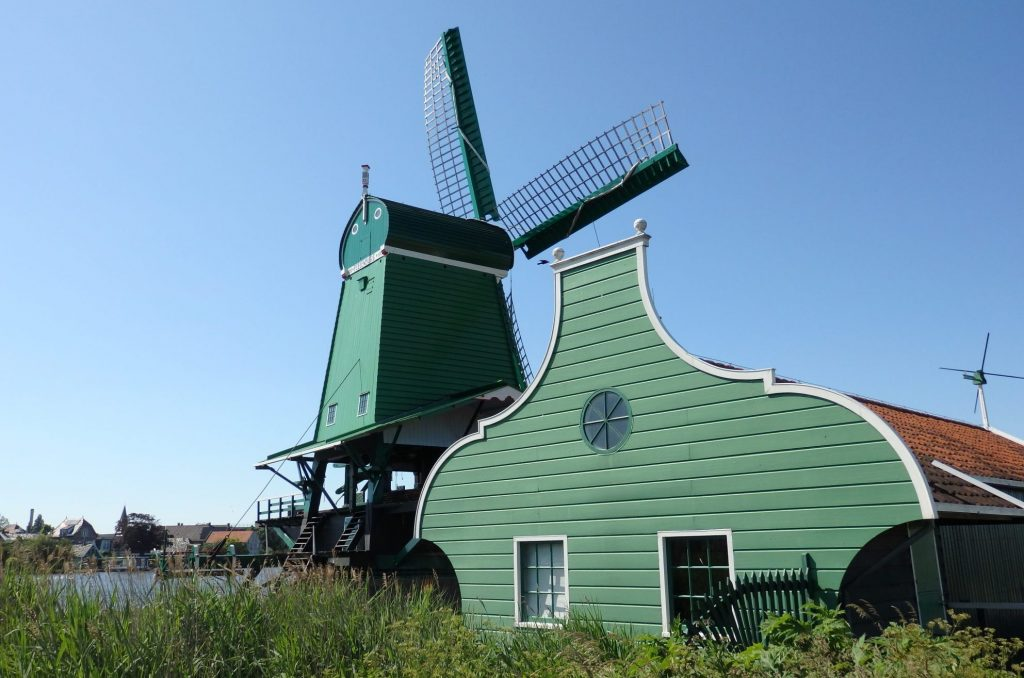 Two buildings: In the foreground a low building with a rounded facade that rises to a tall flat shape above the roofline, only one story tall, painted green on the front facade. Behind, the windmill is on stilts, four-sided, painted green, the walls slanted so it's bigger at the bottom than the top. The windvanes are on the other side from this view.