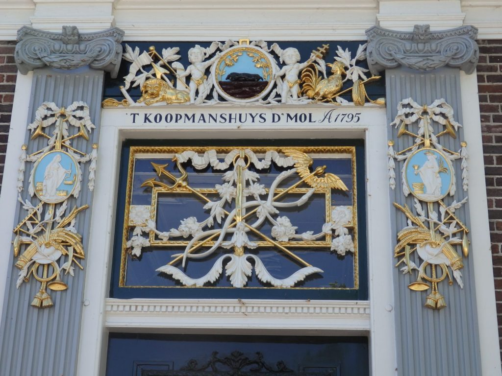 """In the square above the door as well as above and beside it are some lavish carvings: feathers, arrows, banners of all sorts, mostly in white or gold. Above the door frame it reads """"'t Koopmanshuys d'Mol A1795."""""""