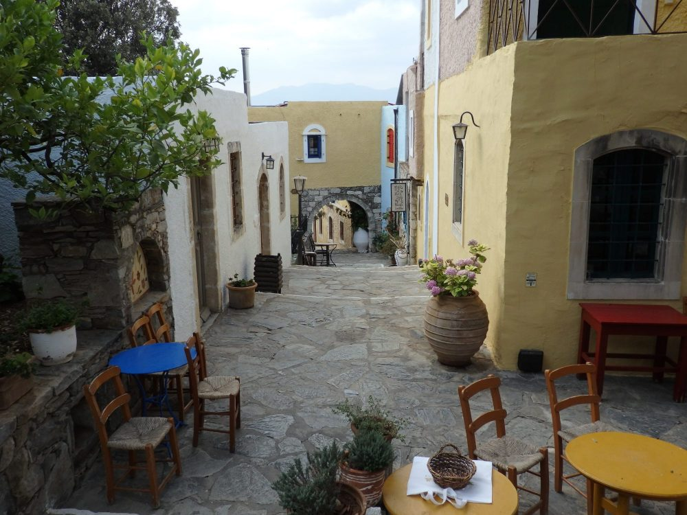 """A """"street"""" in Arolithos Traditional Cretan Village. The street is stone paved, with tables and chairs in the foreground. It slants downwards straight ahead, with some stairs down. On either side are low buildings painted white or light yellow."""