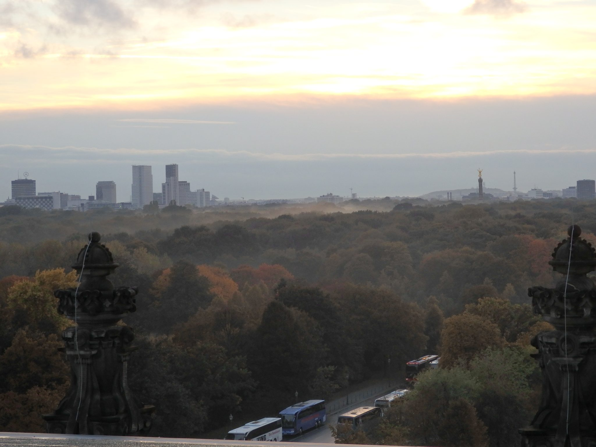 """Our sunset ended in a bank of clouds on the horizon. In the foreground, the Tiergarten park. The buildings in the distance on the left are the """"City West"""" district around Kurfurstendamm. The pillar on the right is the Victory Column at Grosser Stern."""