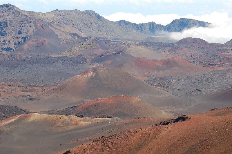 Haleakala Crater in Maui. It's a brown and reddish landscape of hills and valleys, up to higher brown hills in the background. Photo courtesy of Nat Harris.