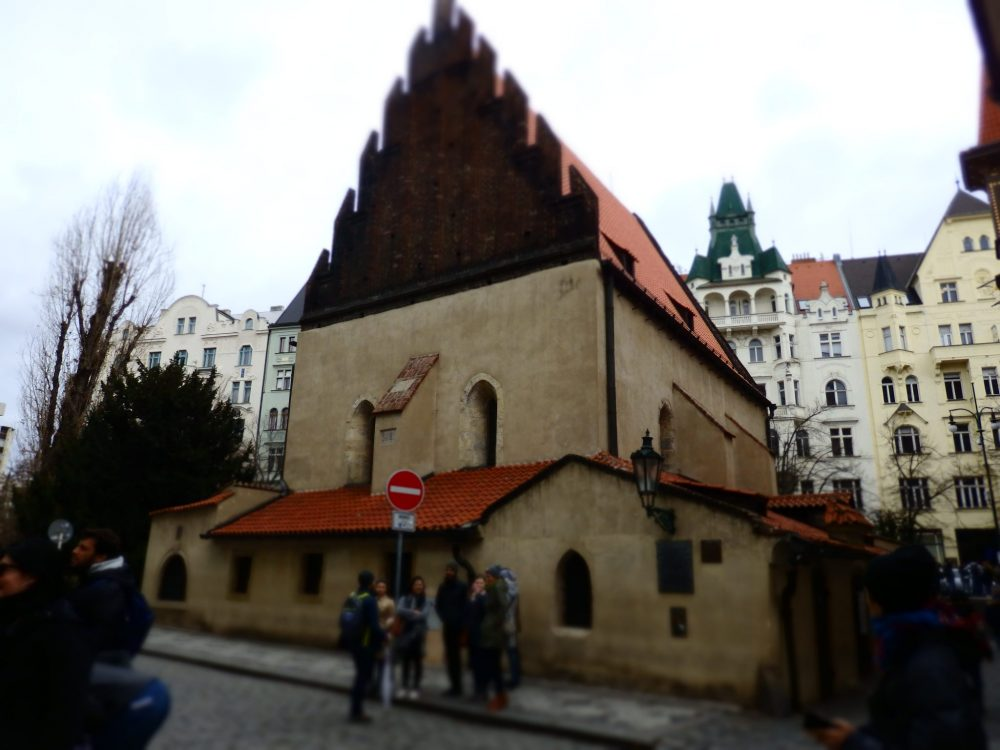 One of the synagogues in Prague, the Old-New synagogue is plastered in an off-white color. The roof has a high peak and there are only a few arched windows.