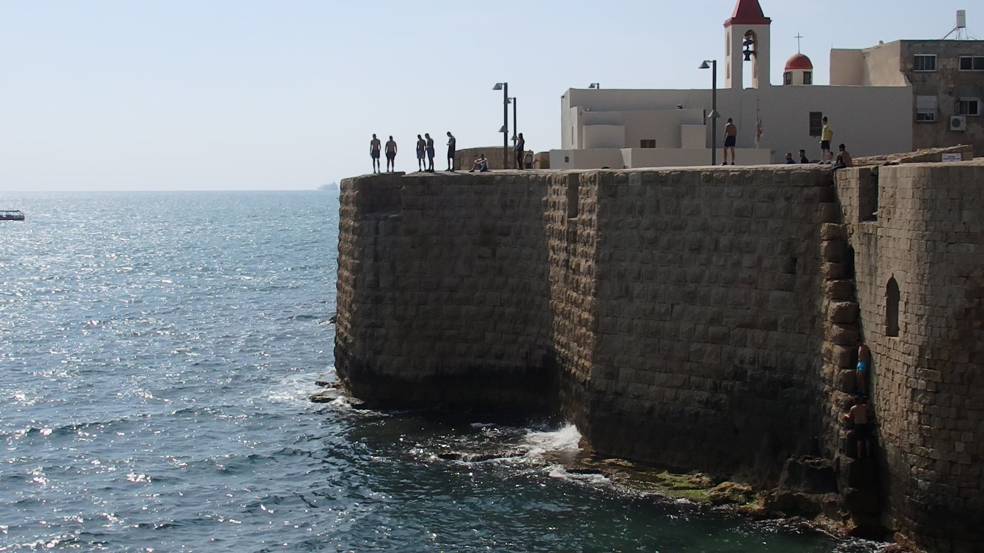 A view of the wall around Akko old city. Notice the boys preparing to jump from the wall, and, on the bottom right, a couple of boys climbing up from the water.