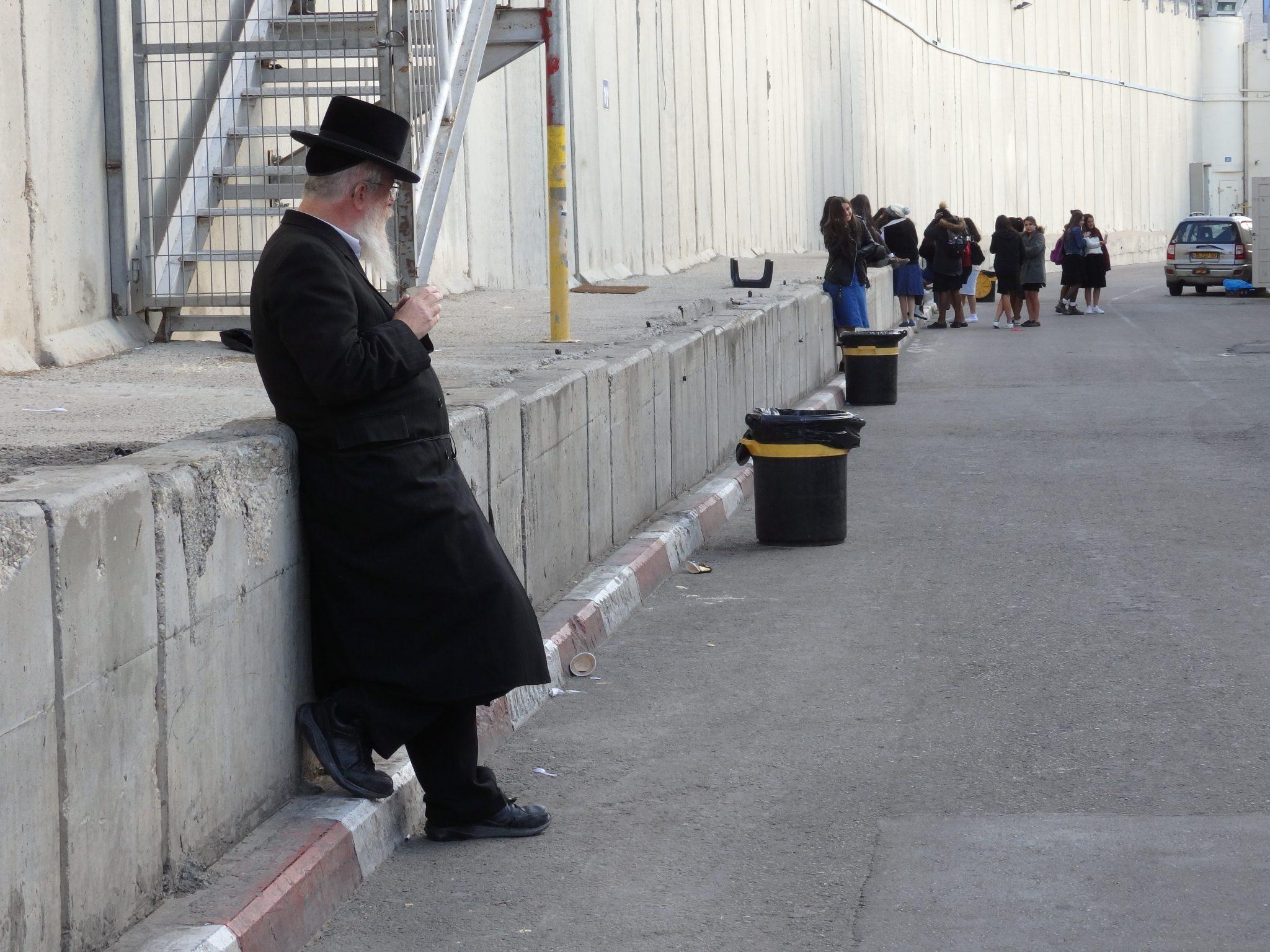 An Orthodox Jew takes a break outside Rachels Tomb