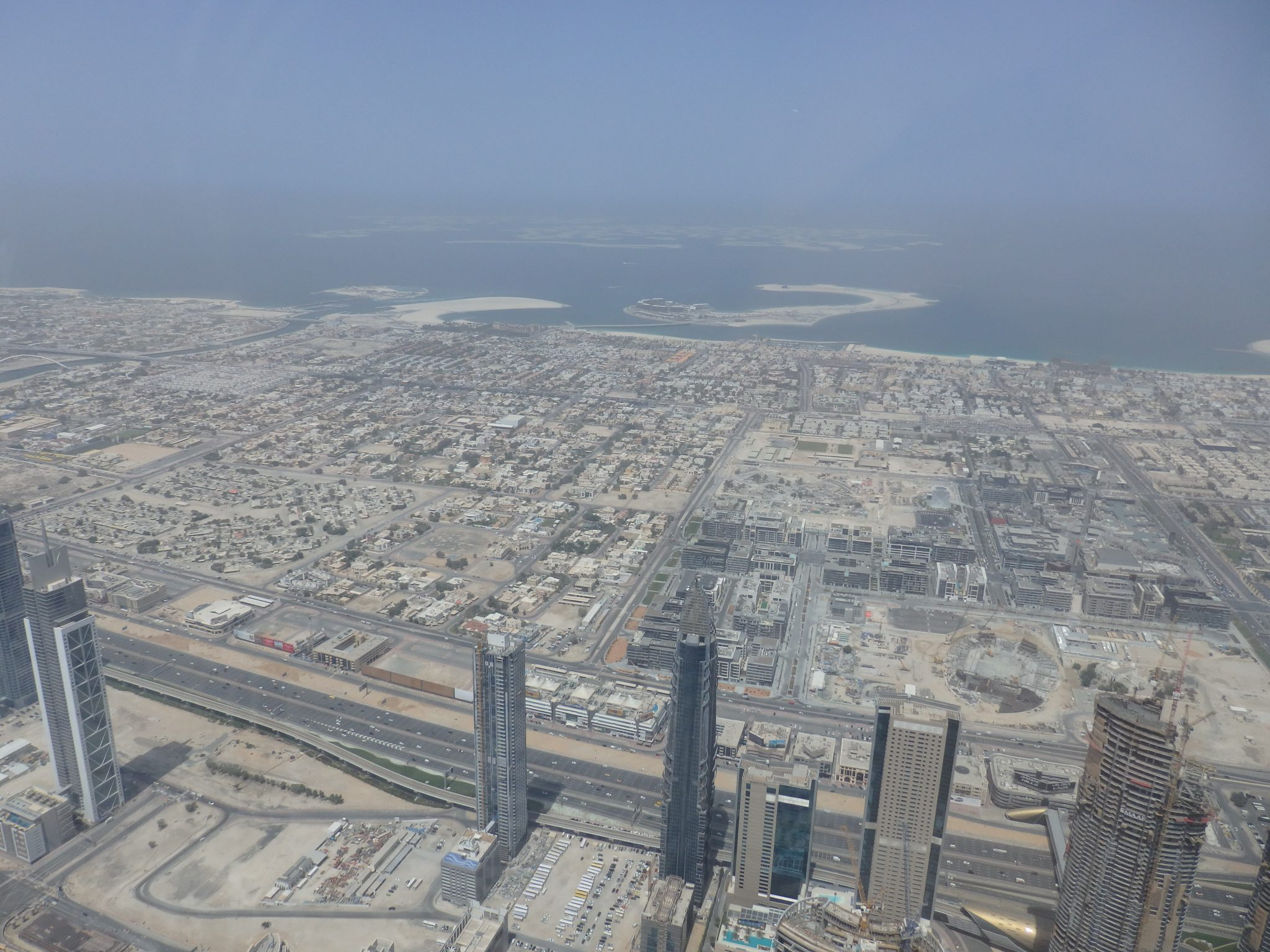 "Here you can see a lower-rise area of Dubai, mostly housing. In the dim distance is the coast, and beyond it are the artificial islands called the ""World Islands"". Visiting Burj Khalifa"