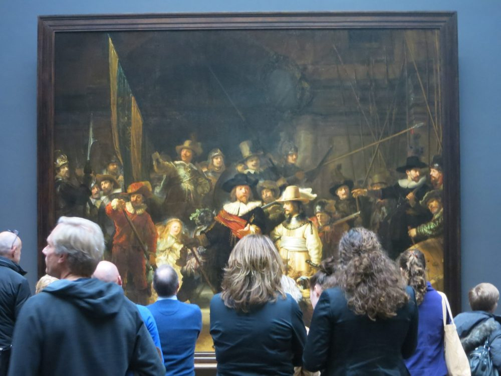 The painting of The Night Watch fills the background. In front, a crowd of visitors, backs to the camera, views the painting.