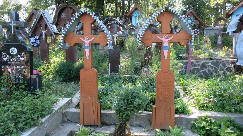 graves in Ieud cemetery, with simply painted crucifixes and metal roofs. The Wooden Churches of Maramures