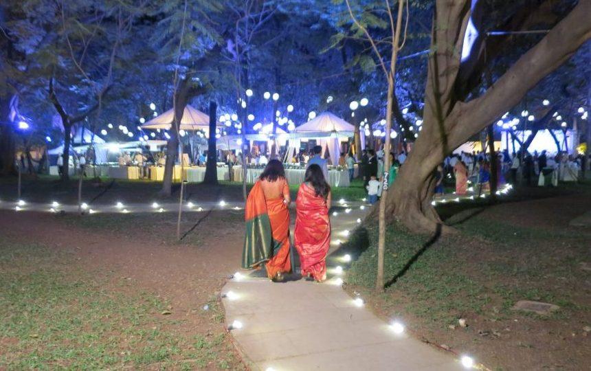 Women in colorful saris walk toward a wedding reception in the garden of our hotel.