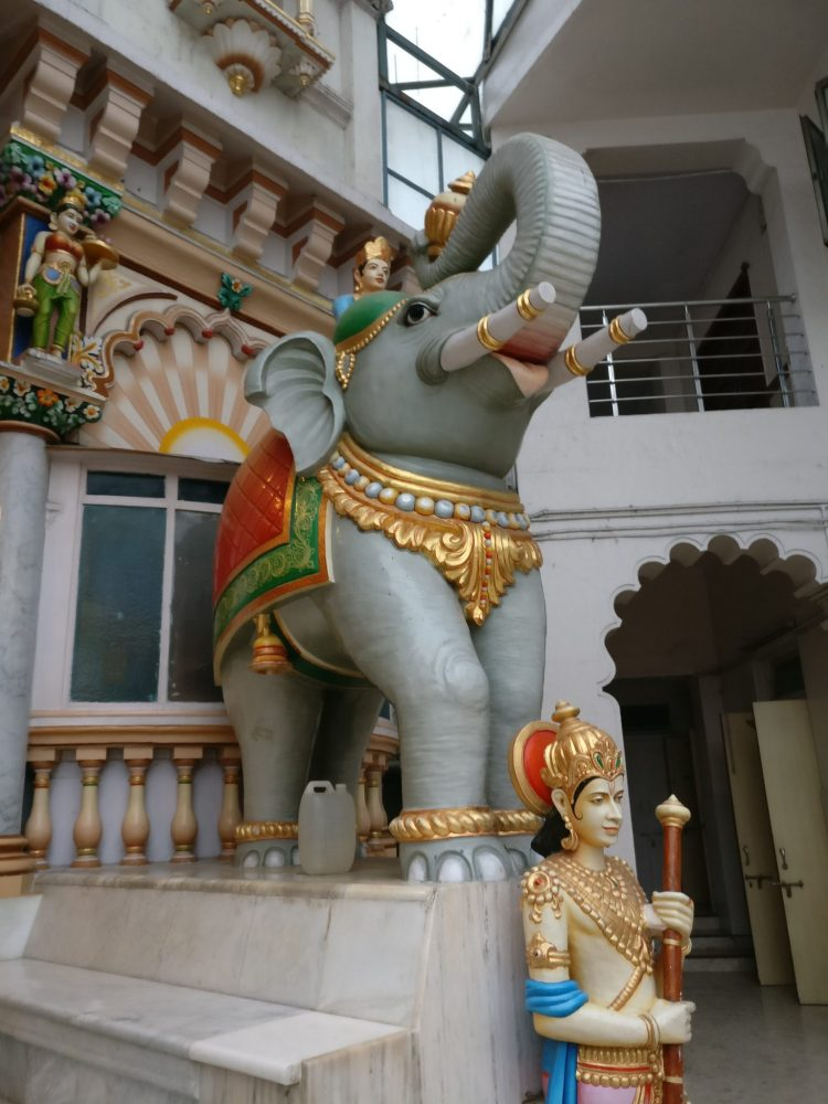 The elephant statue in front of the Jain temple is guarded by a figure with a very expressive face. Mumbai sightseeing