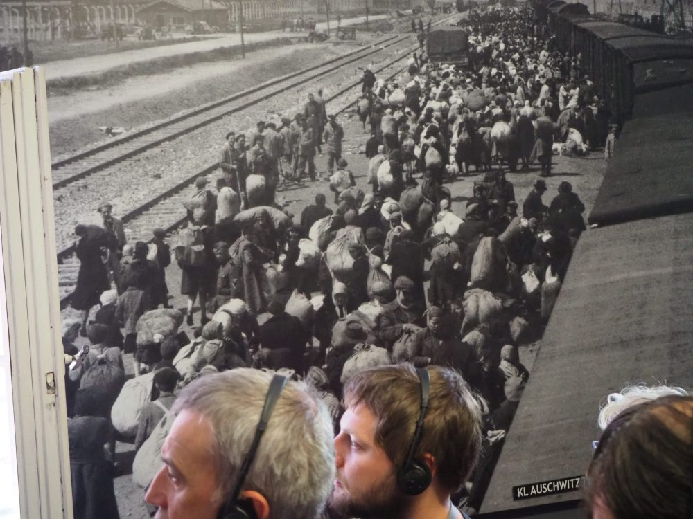 Three or four people can be seen in color at the bottom of the picture, with headphones on. Behind them and filling the rest of the picture is a black and white photo of a crowd of people, train on the right of them, tracks on the left of them.