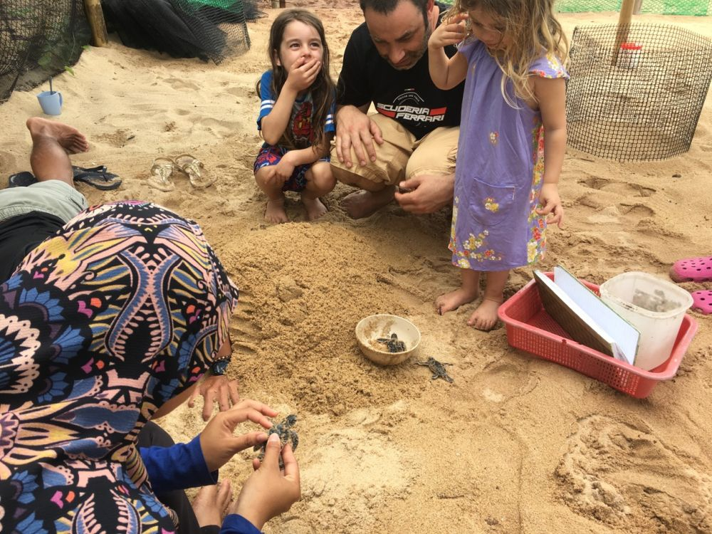 Emma's partner and kids watch as some late hatchlings are excavated from a nest. Photo courtesy of Emma Walmsley.