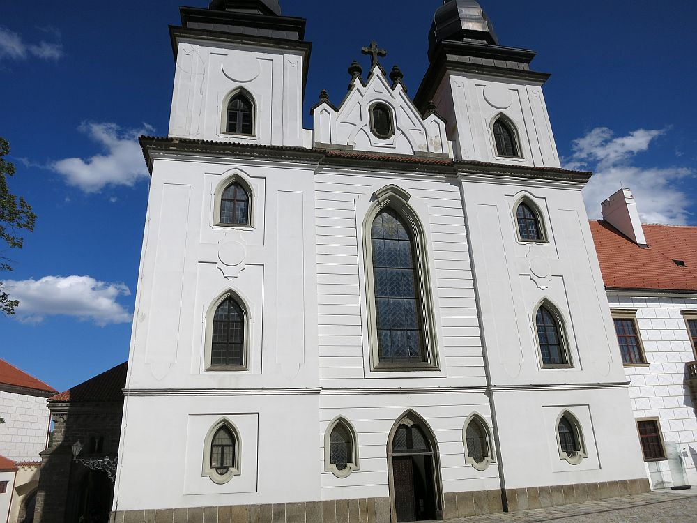 The front is plastered simply in white, with pointed gothic arched windows and two black turrets.