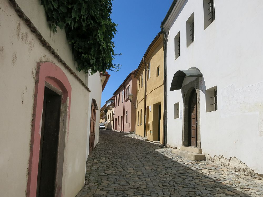 A street in the old Jewish Quarter of Trebic, Czech Republic: the street is cobbled, and the houses (all just 2 stories) have simple flat fronts with a door and square windows. Only one is visible on the left: off-white with a pink door frame. On the right the nearest is plain white, the next mustard yellow and the one after that is pastel pink.