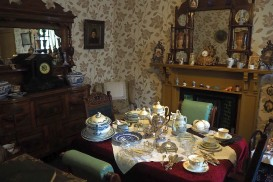 A dining room in Wick Heritage Museum. Notice the sheer quantity of dishes and other objects on the tabel and mantel.