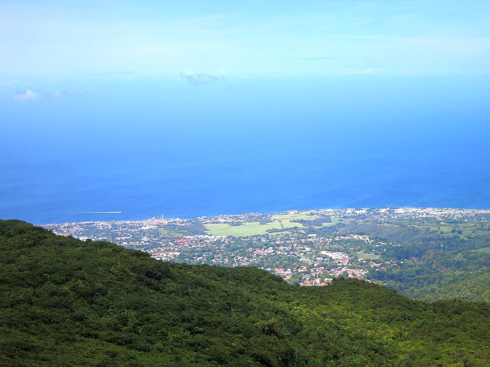 A view from the side of La Soufriere volcano in Guadeloupe shows a very green landscape, a village on the sea, and deep blue water.