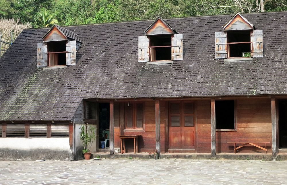 The master's house at La Grivelière coffee plantation in Guadeloupe: It has a weathered wood ground floor with a shallow porch and simple poles holding up the roof. The roof is dark brown shingles and the second floor windows stick out in dormer windows from the roof. Each dormer window has small shutters, which are open, also weathered wood.