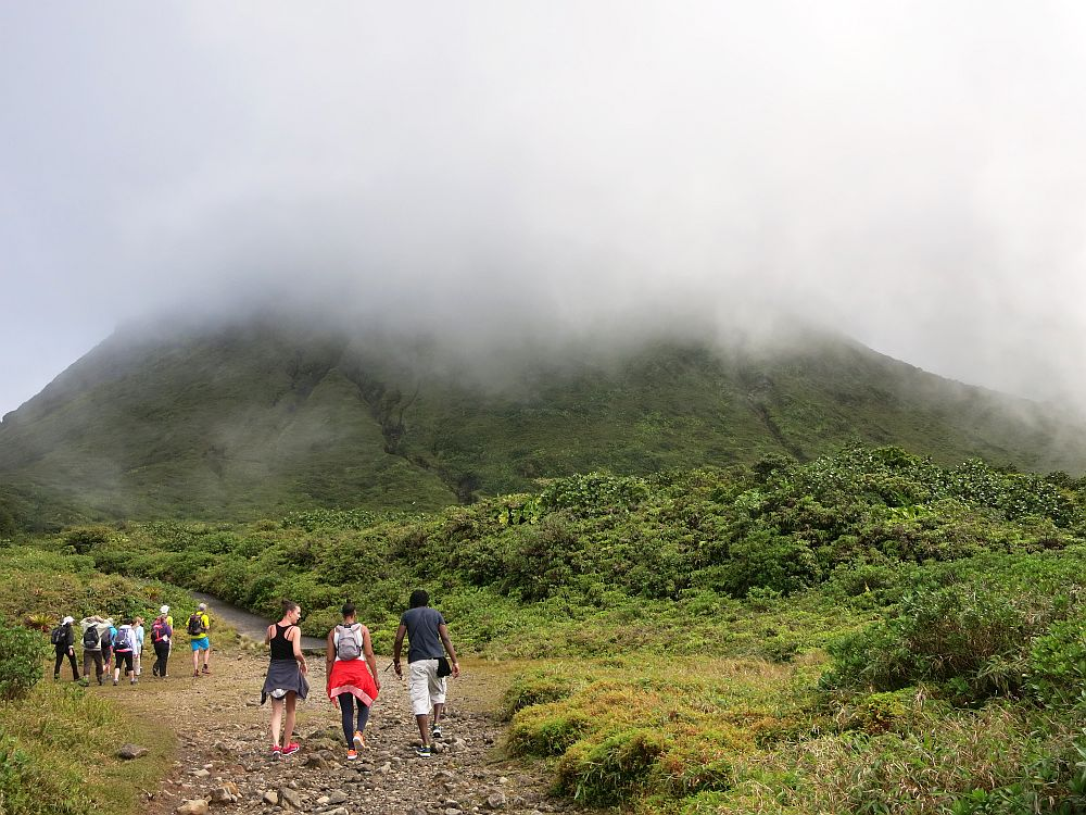 In the foreground, three people walking away from the camera on a wide dirt trail. Beyond them, a group of more people. Beyond them is the green bump of the mountain, most of which is obscured by cloud.