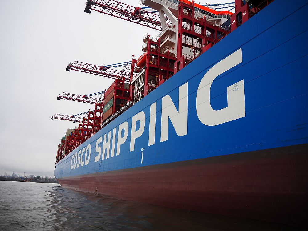 "A close view of the side of a container ship, reading ""Cosco Shipping"" on the side, with large cranes extending over the side of the ship."