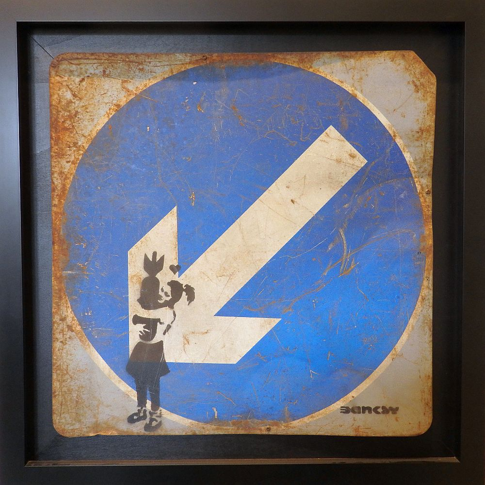 On a traffic sign of a white arrow on a blue background, the stencil shows a young girl hugging a rocket.