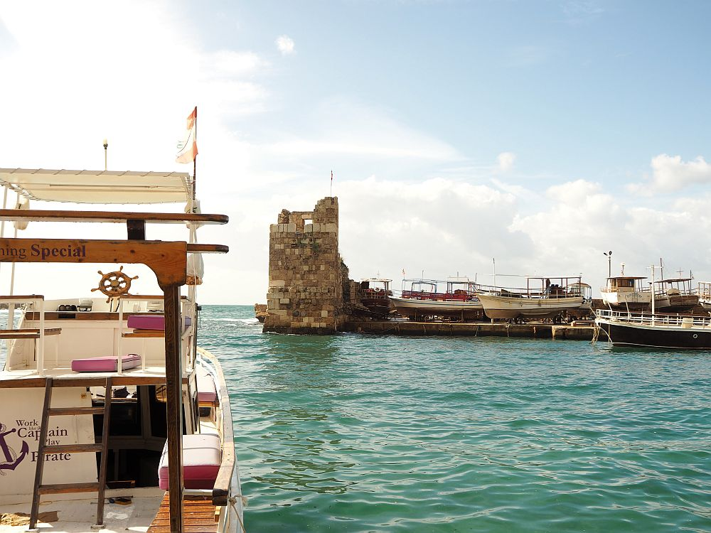 A partial view of the little Byblos harbour, with an ancient tower guarding the entrance. A moored tourist boat in the foreground.  Special places in Lebanon: Byblos harbour.