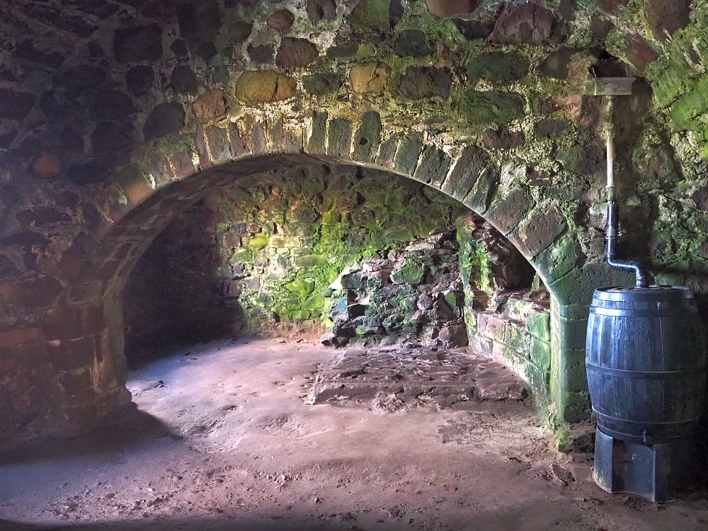 an archway shows what remains of a hearth and a dirt floor in the Dunnottar Castle kitchen.