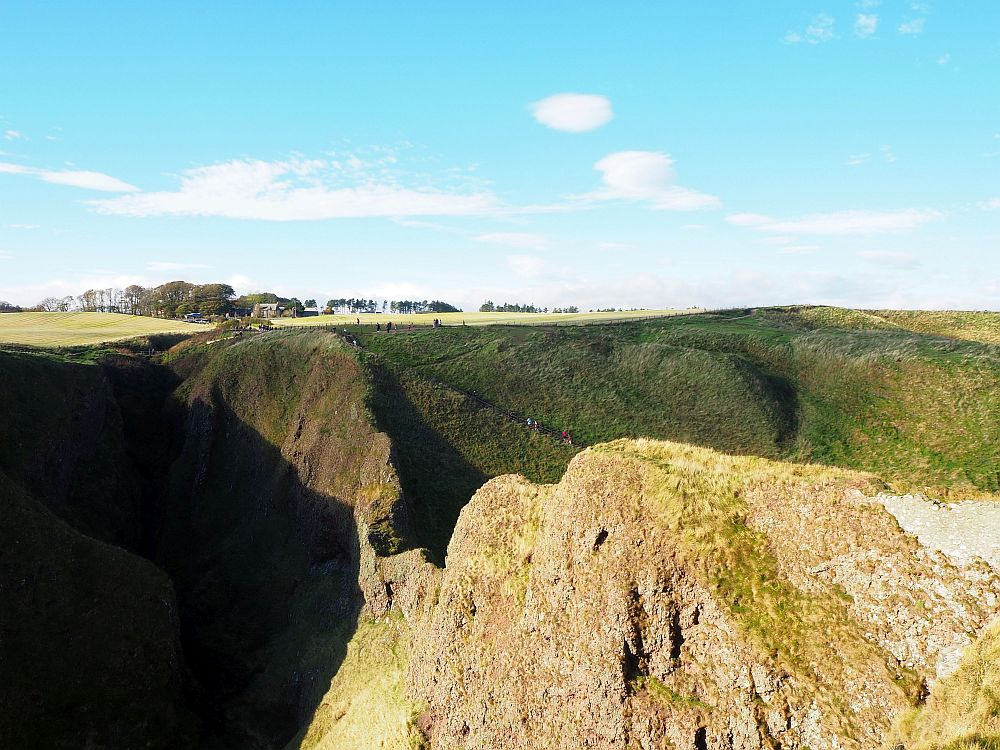 In this view from Dunnottar castle, you can see the ridge of land that connects the castle to the mainland. If you look closely, you can also see the stairway visitors use to get to the castle from the parking lot: down the stairway and then back up to the castle.