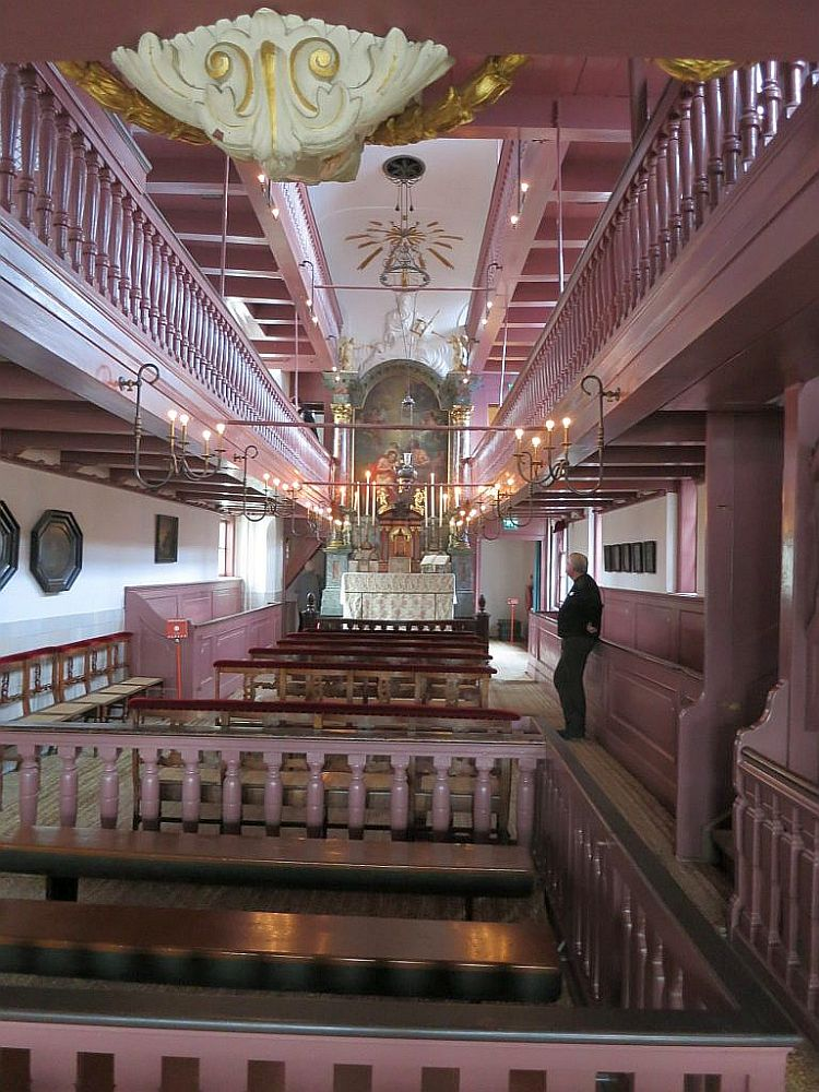 The Ons Lieve Heer op Solder church is a high and narrow space and mostly painted pink: pews down the middle, balconies along both sides above, altar at the far end.