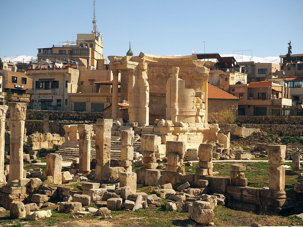 A cluster of ruins with modern buildings in the background. The largest ruin in the middle has a rounded back wall and column forming a circle. It stands on a pedestal with steps leading up to it. The ground around it has lots of pieces of stone columns, some taller, some just small stubs.