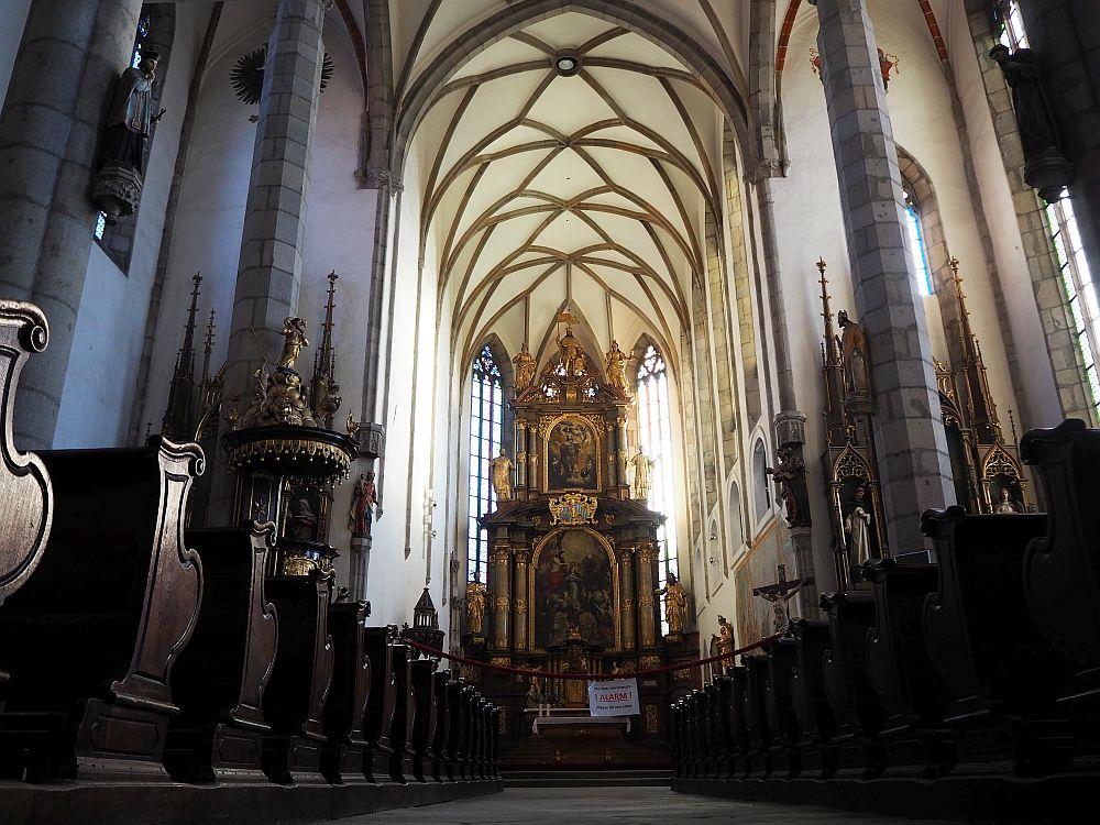 The gothic interior of St. Vitus Church in Cesky Krumlov has an enormous baroque altarpiece.