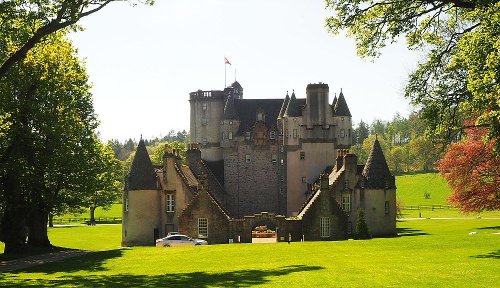 Set on a flat site, Castle Fraser has a tall section at the back of this view and lower wings circling a court in front.