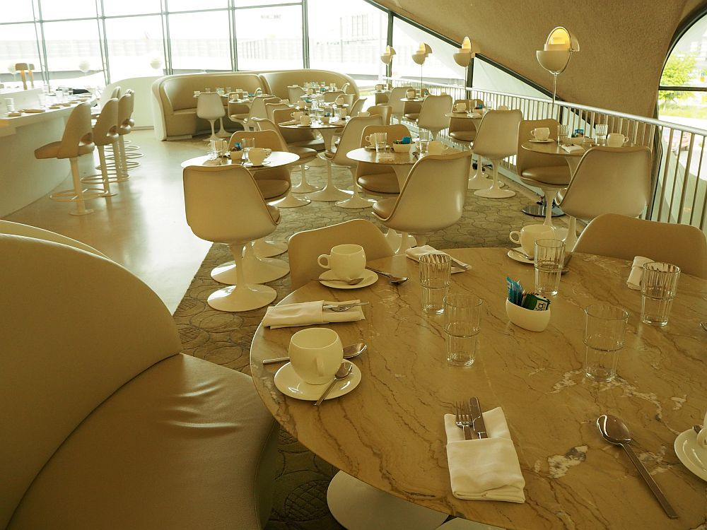 The restaurant is all in whte and light brown, with pedestal bucket chairs.