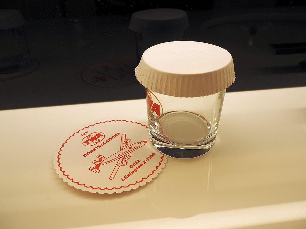 """In the bathroom, a glass with the TWA logo and a coaster that reads """"Fly TWA Constellations. Call LExington 2-7100."""