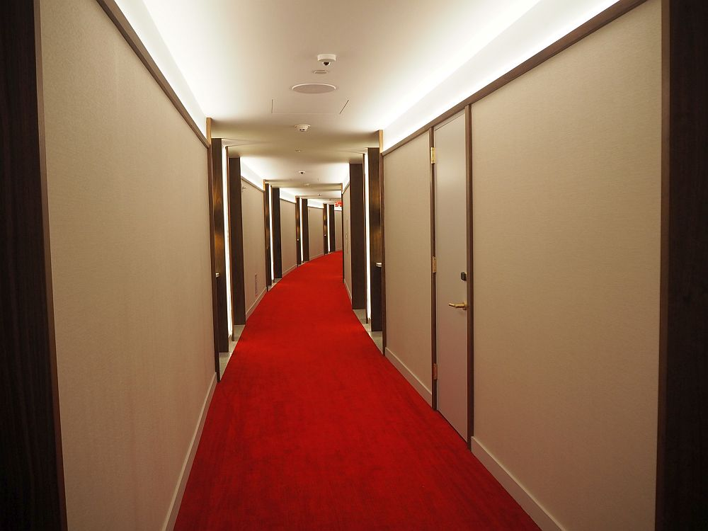 The hall is white-walled and red-carpeted and curves gently to the right.