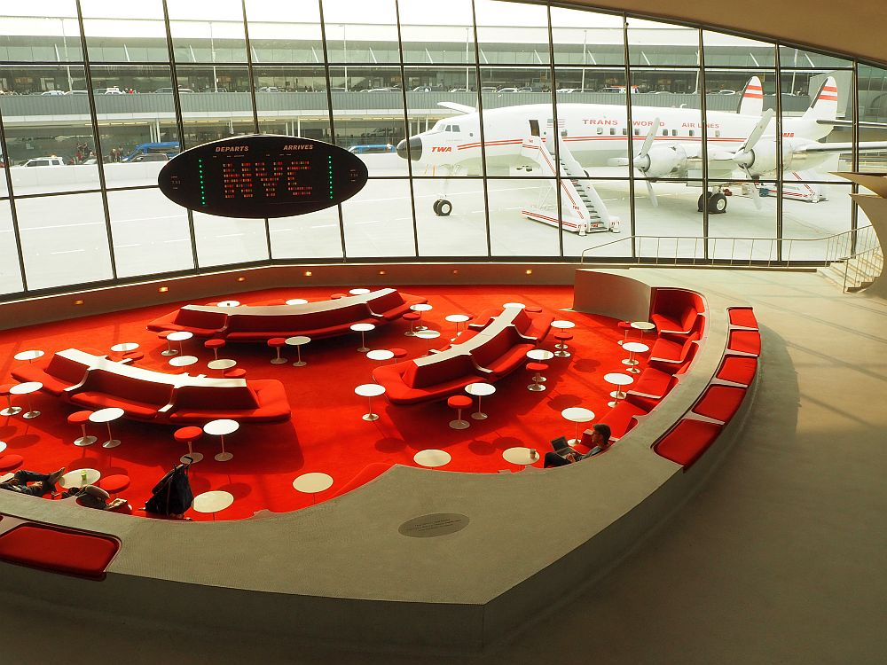 The lounge is carpeted in bright red, dotted with small white tables and red-upholstered benches. Light enters through a wall of large windows, behind which the Connie is visible.