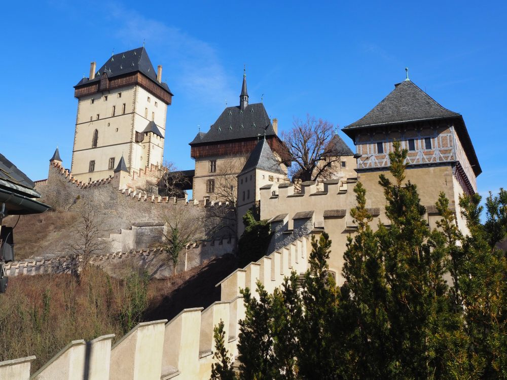 This view from one end of the castle shows three towers, the tallest of which is the Great Tower. The walls are off-white and the roofs are grey. Visiting Karlstejn Castle from Prague