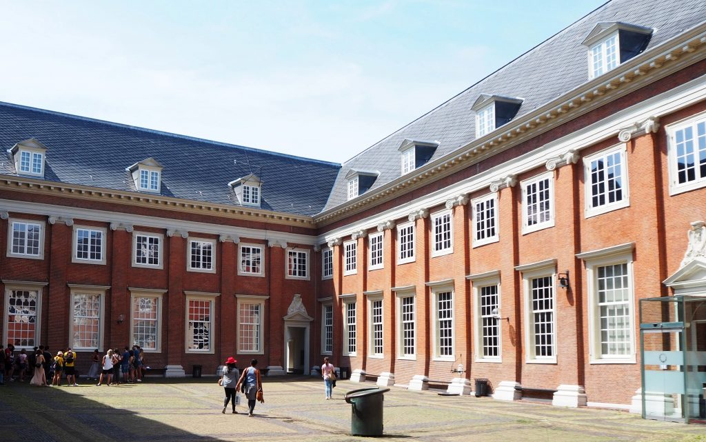 This photo shows two sides of the courtyard: two story buildings with a further story under the roof. The walls are simple red brick with columns, also brick, between the windows.