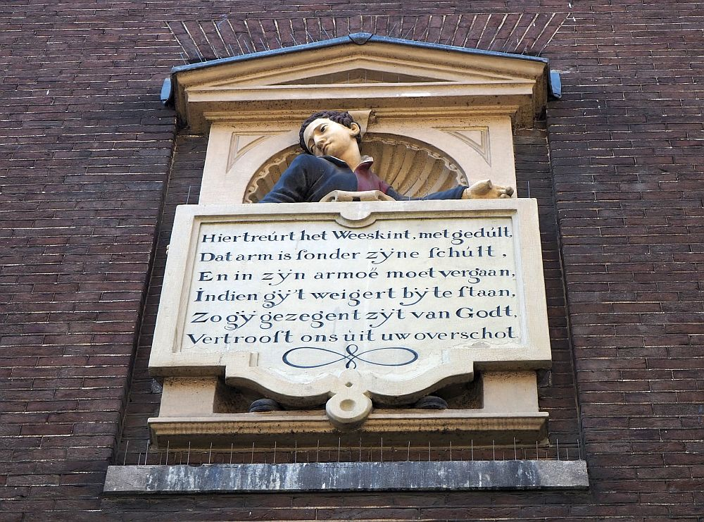 This image is set high on the wall to the side of the entrance to the Amsterdam Historical Museum. Above the verse is the torso of a boy, looking sadly to the side.