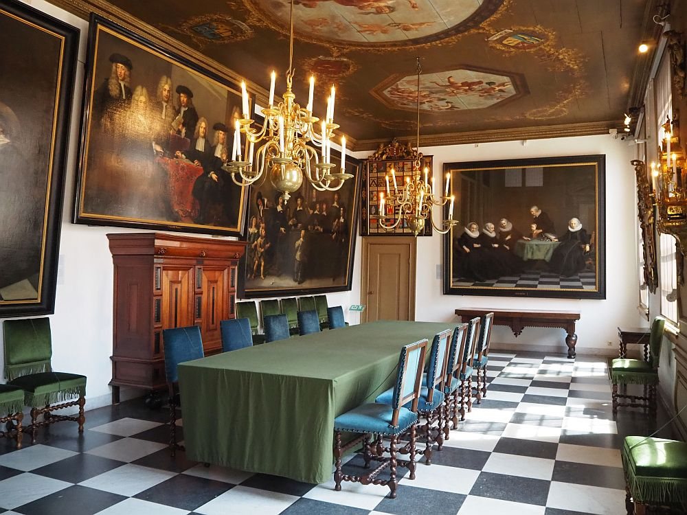 The regents' room at the Amsterdam historical museum is quite grand, with a table down the middle and a chandelier above it. The walls hold large paintings of regents.