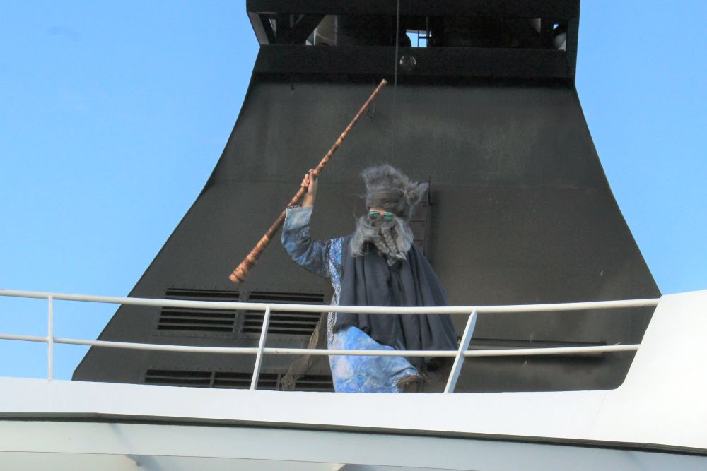 A person standing on the top deck above the photographer, dressed in a blue robe with a black cape, wearing a large fake gray beard and hat and sunglasses, waves a staff.