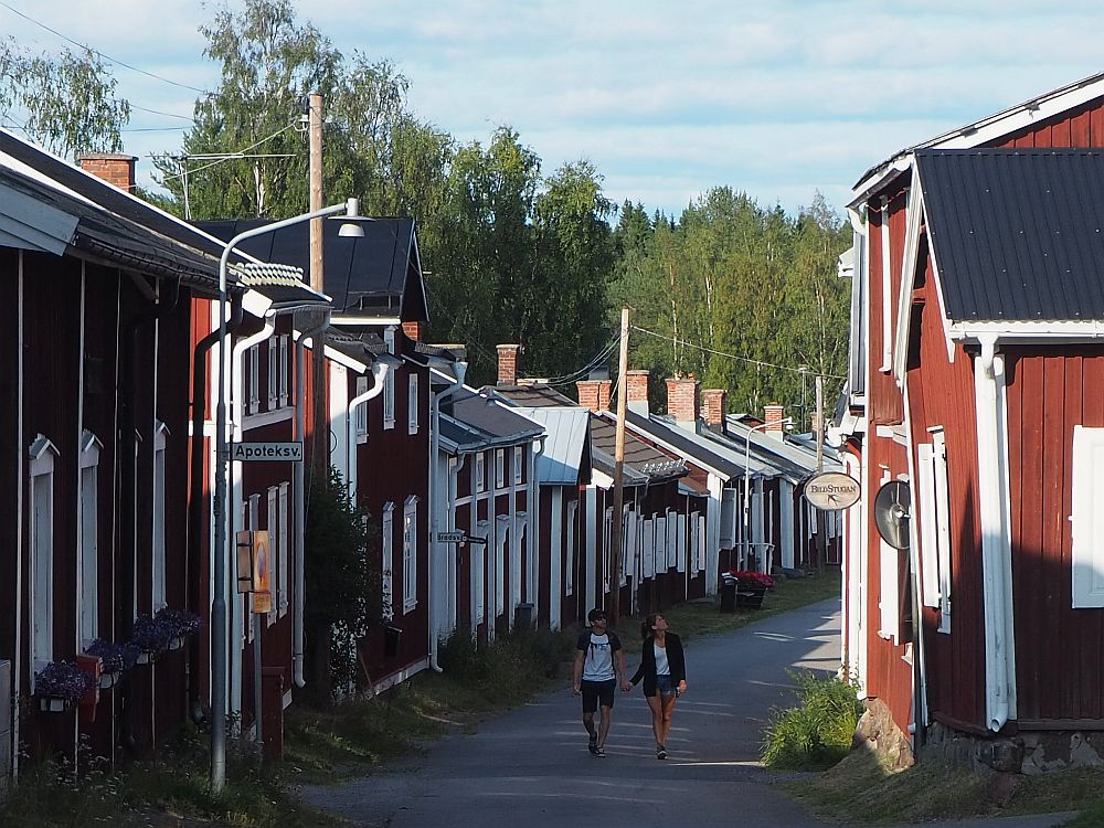 A young couple holding hands walks toward the camera along a road in Gammelstad church town, lined on both sides with small red houses, all very close together. The road turns out of sight to the right behind them.