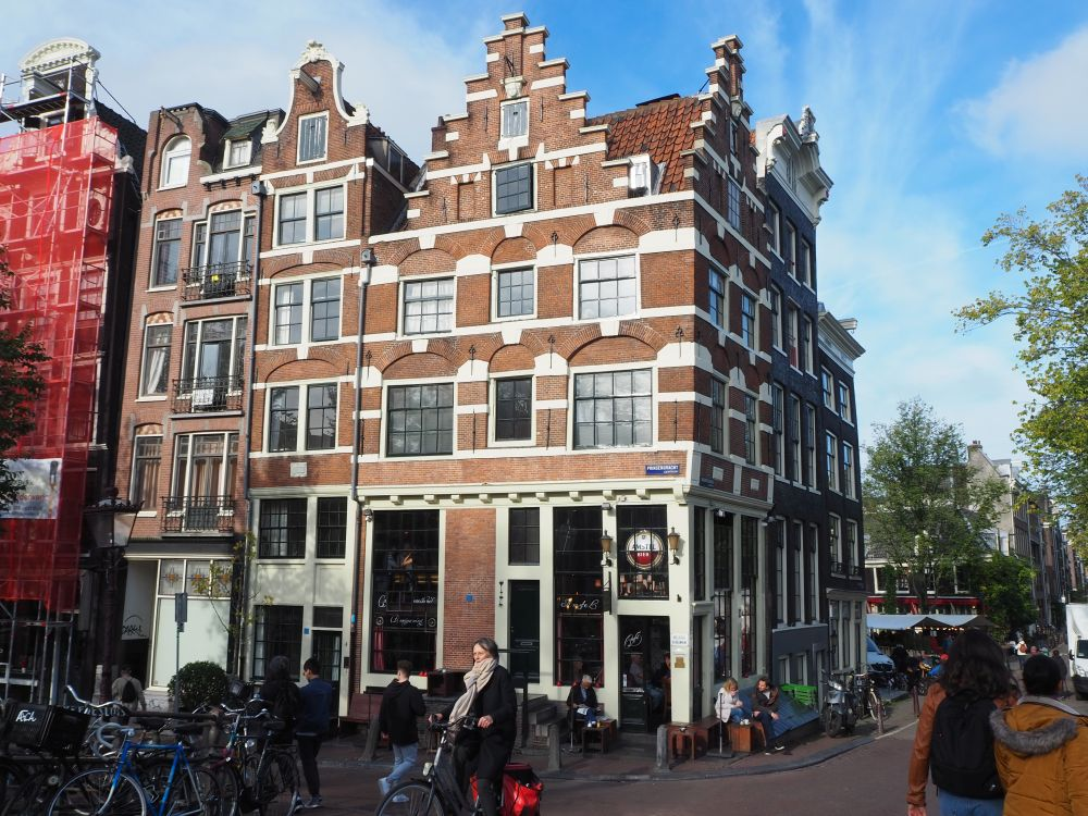 A pretty corner building, 4 stories high, red brick with white details and a pretty stepped gable.