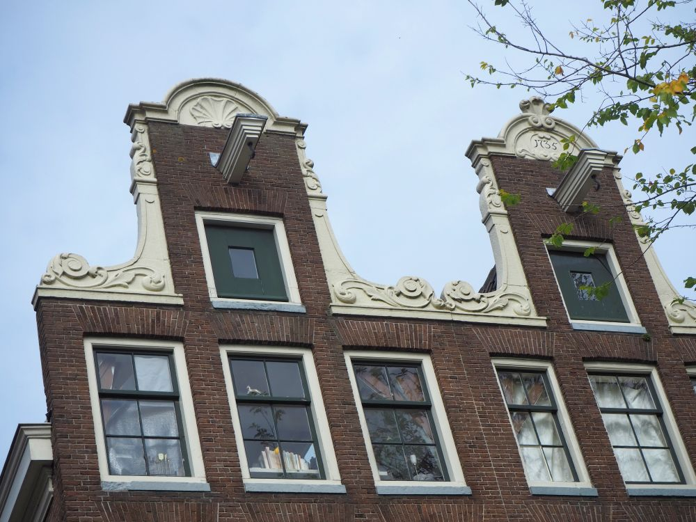 These two gables are vertical red-brick rectangles, but each has a white decorative element surrounding it, with curls at the base, a pillar-like shape on either side, and an arch above the window. The arch on the left gable has a shell shape. The arch on the right has the date: 1735. Each gable has a beam sticking out with a hook on it.