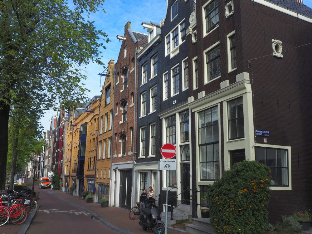 Looking down a row of typical Amsterdam rowhouses: brick with white windows, which we passed on the Jordaan food tour.