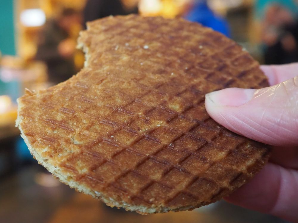 close-up of a round stroopwafel with one bite already taken out of it.
