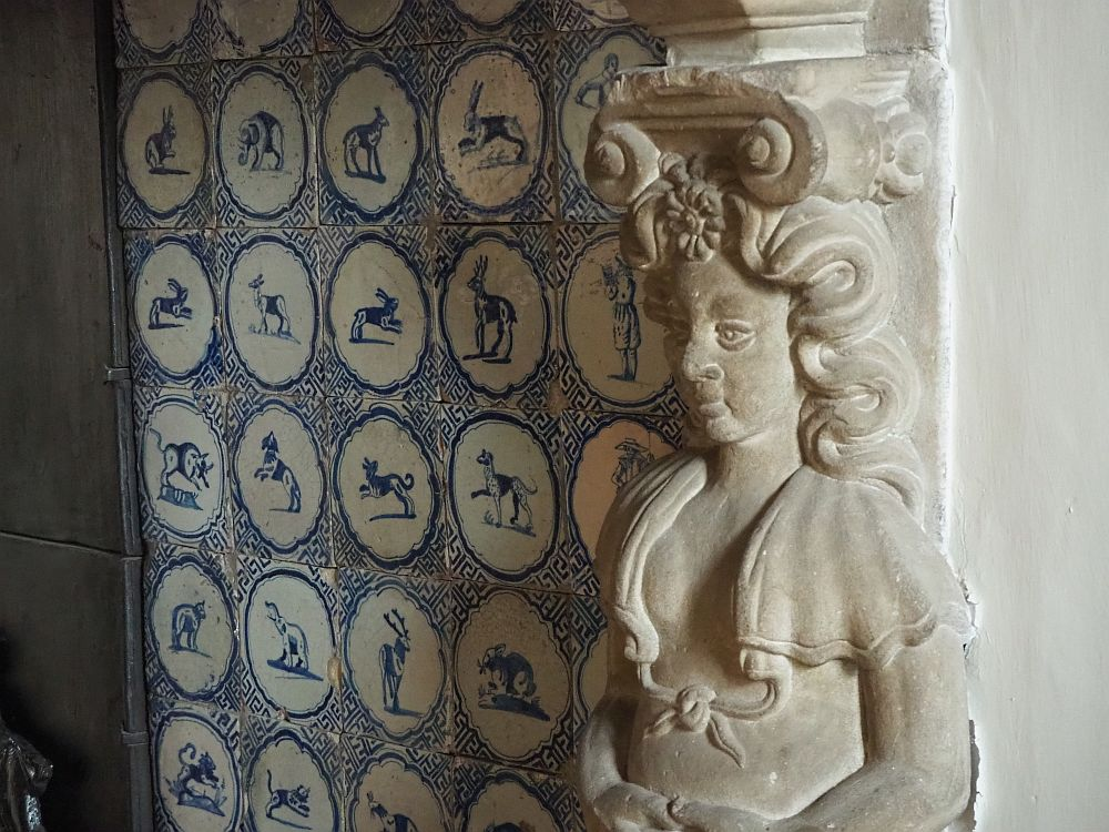 This detail shows a carved woman from the waist up. She's carved of white stone and serves as a column holding up the mantal. To her left is the back wall of the fireplace, tiled with blue and white delft tiles. Each has a picture of an animal: many are dogs or rabbits.