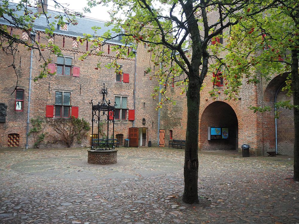 The courtyard is cobbled with stone. The wall beyond is red-brick and studed with occasional windows with red shutters. A tree stands in the foreground and a round well behind that. On the wall on the right is an arched gateway.
