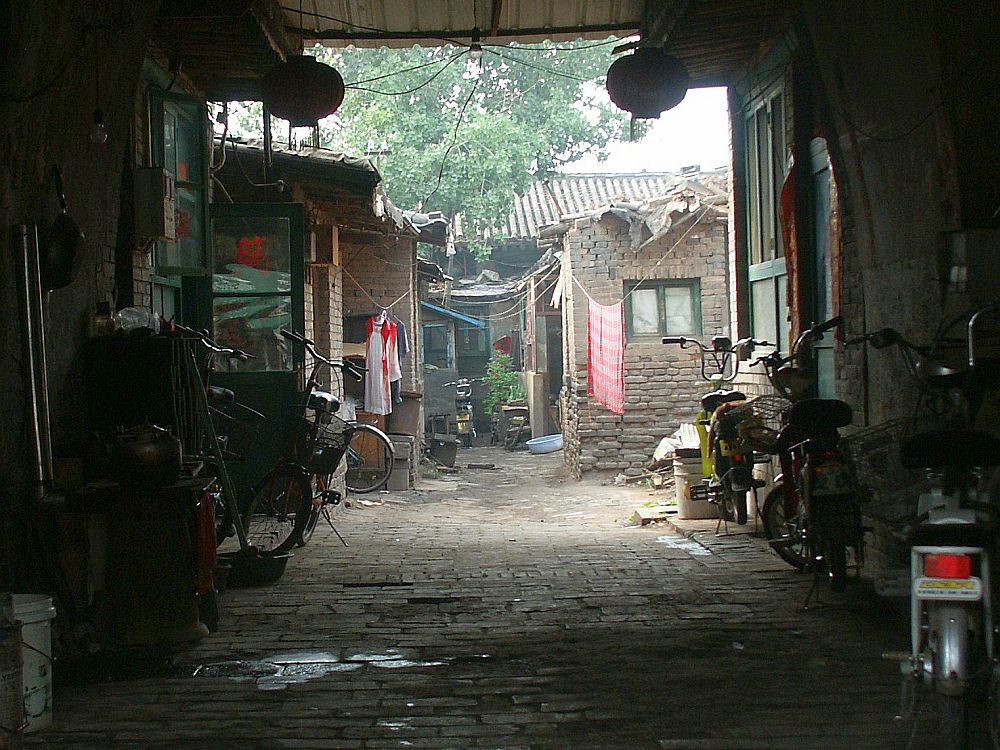 Inside the archway, several bicycles are parked against the side walls. The floor is paved with bricks, wet in places. Beyond the archway is a space that is open to the sky. A row of brick shacks face the center alleyway. Their bricks are rough and their roofs, the bits that are visible, look like they're made of scraps of metal and plastic. Laundry hangs on lines between them.