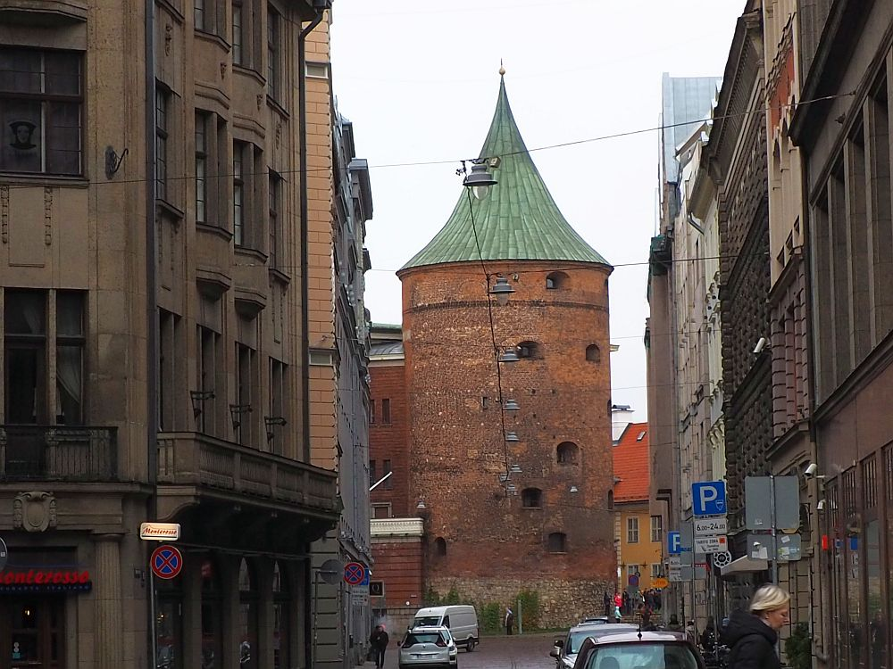 Seen at the end of a short city street, the tower is red-brick, round and several stories high with a green pointed roof. It has only a few small windows.