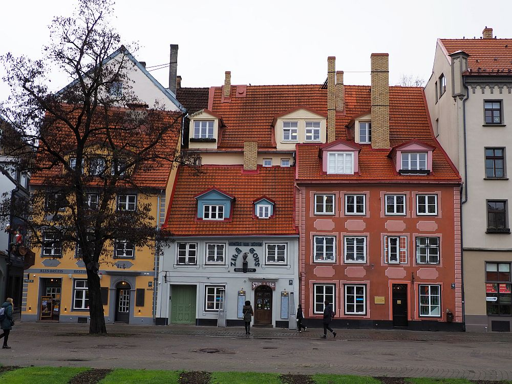 Three houses in a row, right up against each other. the left-hand one is four or more stories with yellow paint. The middle one is 3 stories and is grey. the right-hand one is four or more stories and is ping, with paler pink decorative edging.