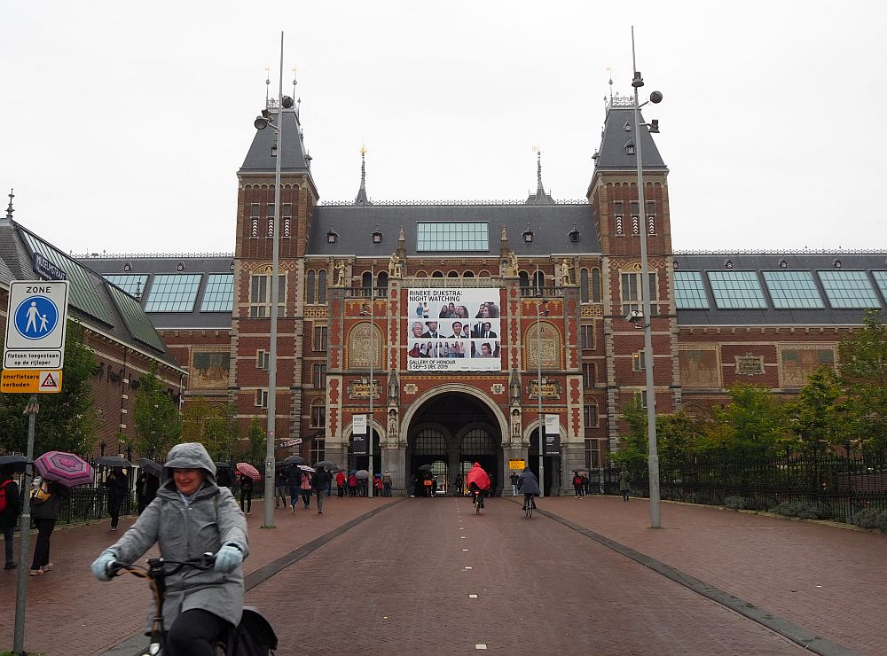 The red-brick museum has a square entrance framed by two turrets. In the center is a large archway, with is the entrance to a bike tunnel through the building. On either side of that is a smaller tunnel for pedestrians. People carry umbrellas on the sidewalk, while people in the bike lane are bundled up against the cold.